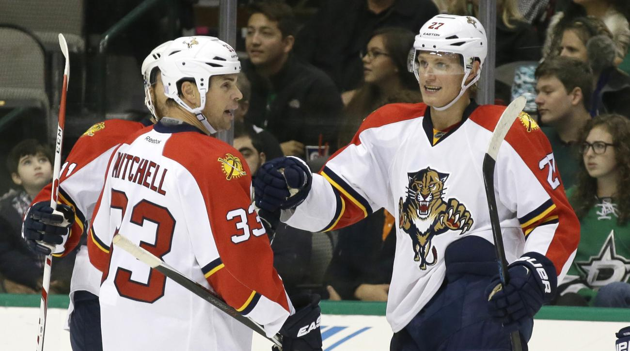 Florida Panthers center Nick Bjugstad (27) celebrates scoring his goal with teammates  Willie Mitchell  and Jonathan Huberdeau (11) during the first period of an NHL hockey game against the Dallas Stars Saturday, Oct. 24, 2015, in Dallas. (AP Photo/LM Ote