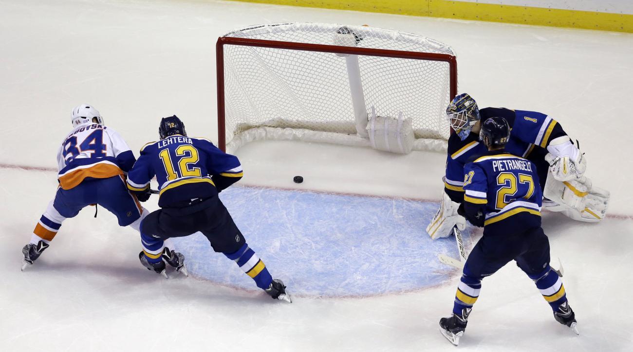 New York Islanders' Mikhail Grabovski, of Germany, scores the game-winning goal past St. Louis Blues goalie Brian Elliott (1), Alex Pietrangelo (27) and Jori Lehtera (12), of Finland, during overtime of an NHL hockey game Saturday, Oct. 24, 2015, in St. L