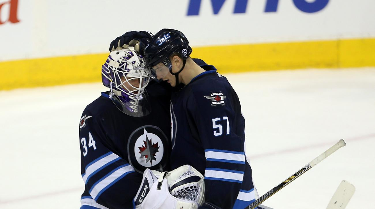 Winnipeg Jets goaltender Michael Hutchinson (34) and Tyler Myers (57) celebrate after defeating the Minnesota Wild during NHL hockey action in Winnipeg, Sunday, Oct. 25, 2015. (Trevor Hagan/The Canadian Press via AP)