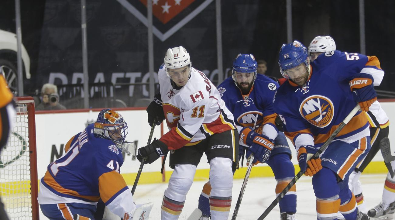 New York Islanders goalie Jaroslav Halak (41) deflects a shot on the goal as Calgary Flames' Mikael Backlund (11) and Johnny Boychuk (55) watch during the first period of an NHL hockey game Monday, Oct. 26, 2015, in New York. (AP Photo/Frank Franklin II)