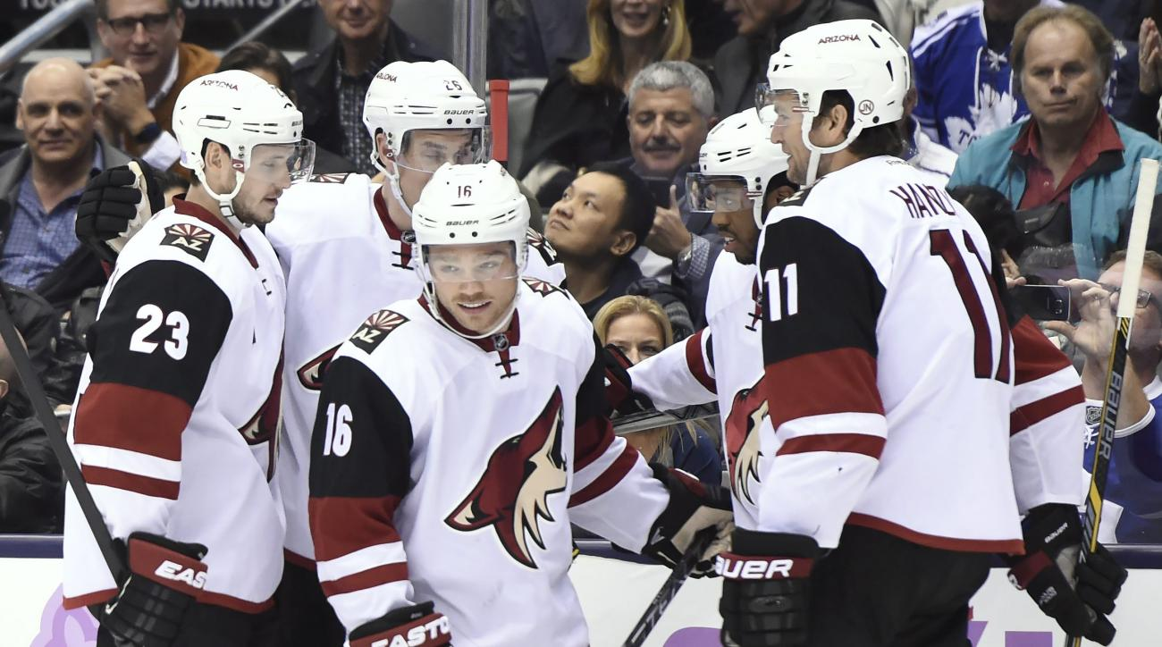 Arizona Coyotes' Max Domi (16) celebrates with teammates Ekman-Larsson, rear left to right, Michael Stone, Anthony Duclair and Martin Hanzal after scoring agains the Toronto Maple Leafs during first period NHL hockey action in Toronto on Monday, Oct. 26,