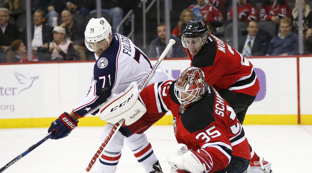New Jersey Devils goalie Cory Schneider (35) blocks a shot as Columbus Blue Jackets left wing Nick Foligno (71) attacks during the second period of an NHL hockey game, Tuesday, Oct. 27, 2015, in Newark, N.J. Devils' John Moore helps defend on the play. (A