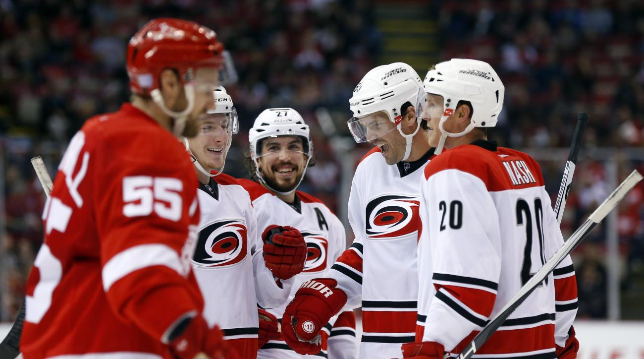 Carolina Hurricanes defenseman Ron Hainsey, second from right, celebrates his goal against the Detroit Red Wings in the third period of an NHL hockey game Tuesday, Oct. 27, 2015 in Detroit. (AP Photo/Paul Sancya)