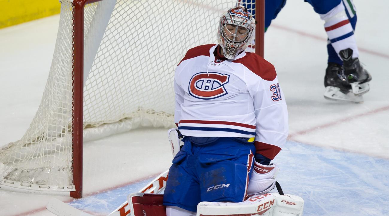 Montreal Canadiens' goalie Carey Price reaches behind him for the puck after making the initial save before being put in the net by Vancouver Canucks' Jared McCann for a goa during the first period of an NHL hockey game in Vancouver, British Columbia, Tue
