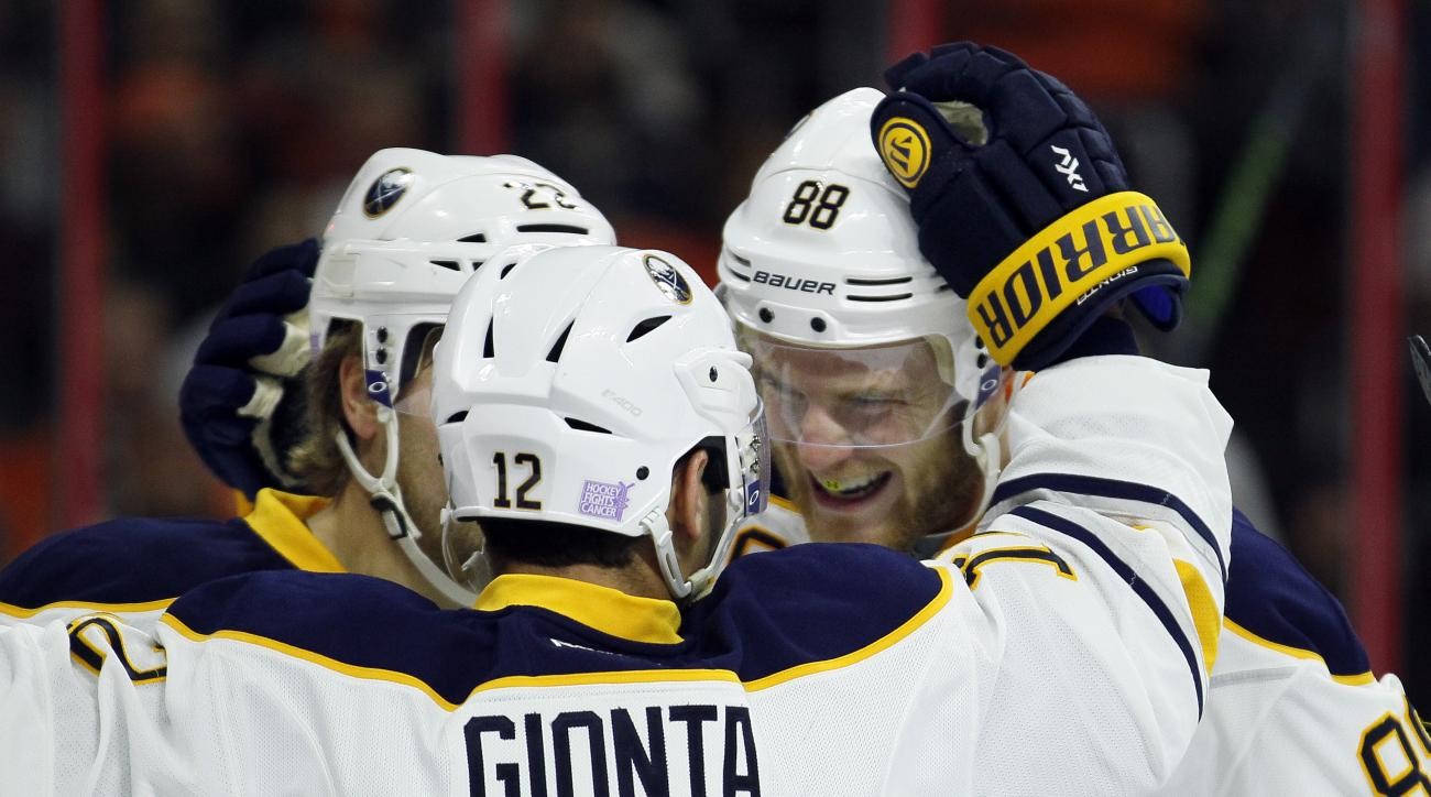 Buffalo Sabres' Jamie McGinn, right, celebrates his goal along with Brian Gionta (12) and Johan Larsson (22) during the first period of an NHL hockey game Tuesday, Oct. 27, 2015 in Philadelphia. The Sabres won 4-3 in overtime. (AP Photo/Tom Mihalek)