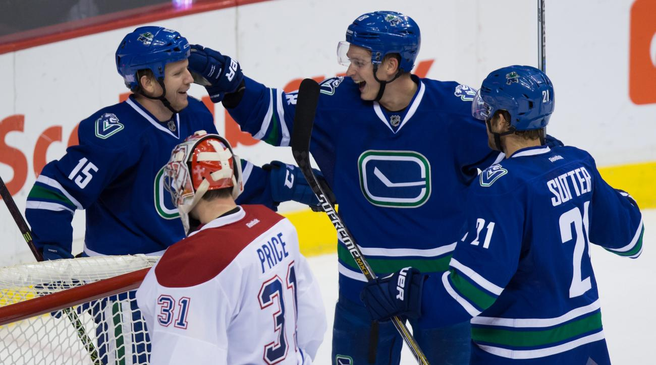 CORRECTS TO THIRD PERIOD FROM SECOND PERIOD - Vancouver Canucks' Derek Dorsett, top, from left to right, Jake Virtanen and Brandon Sutter celebrate Dorsett's goal against Montreal Canadiens' goalie Carey Price during the third period of an NHL hockey game