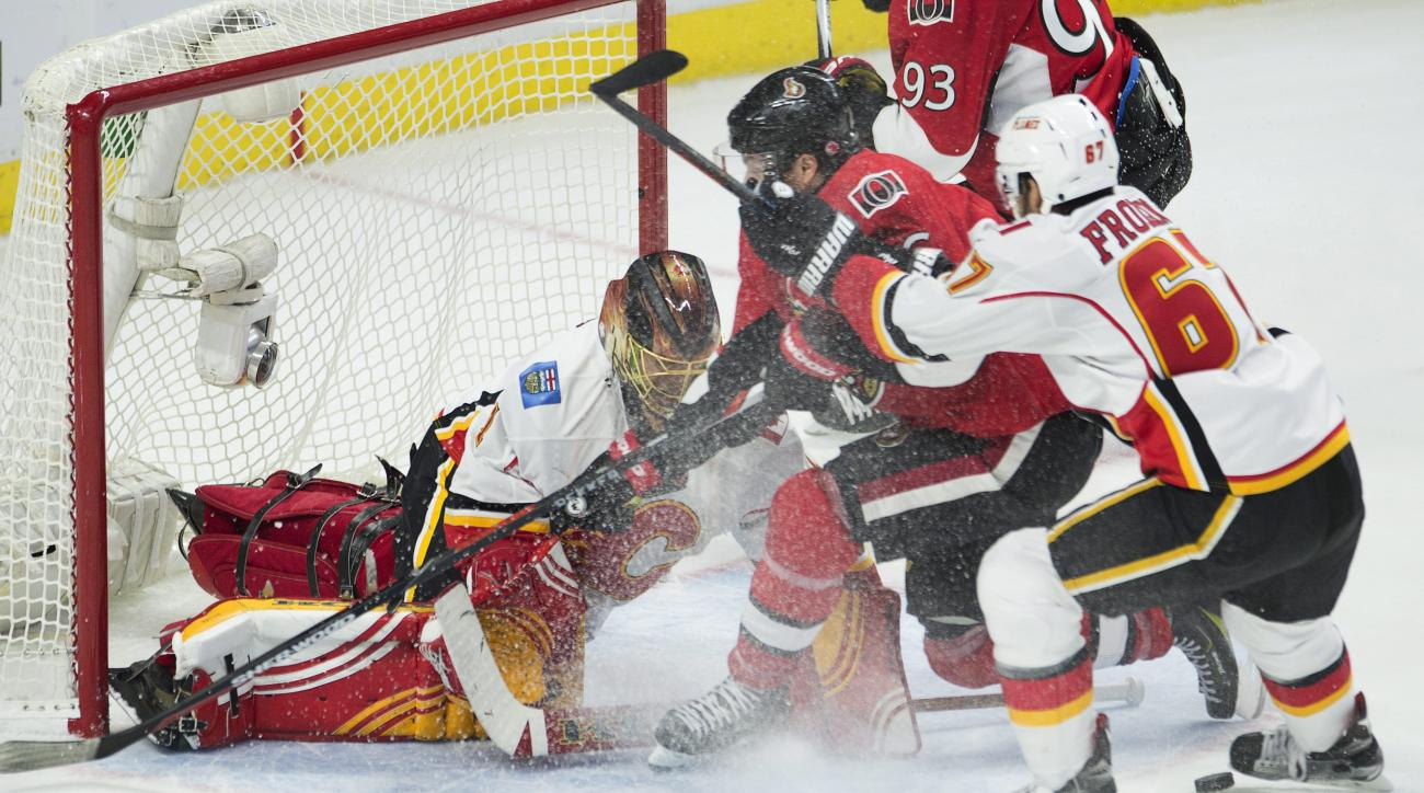Calgary Flames right wing Michael Frolik (67) pushes Ottawa Senators right wing Bobby Ryan (6) towards goalie Jonas Hiller during the third period of an NHL hockey game Wednesday, Oct. 28, 2015, in Ottawa, Ontario. Ottawa won 5-4. (Adrian Wyld/The Canadia