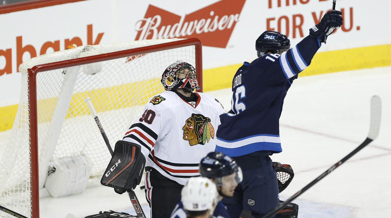 Winnipeg Jets' Andrew Ladd (16) celebrates a goal by Blake Wheeler (not shown) against Chicago Blackhawks goaltender Corey Crawford (50) during first period NHL action in Winnipeg on Thursday, Oct. 29, 2015. (John Woods/The Canadian Press via AP)