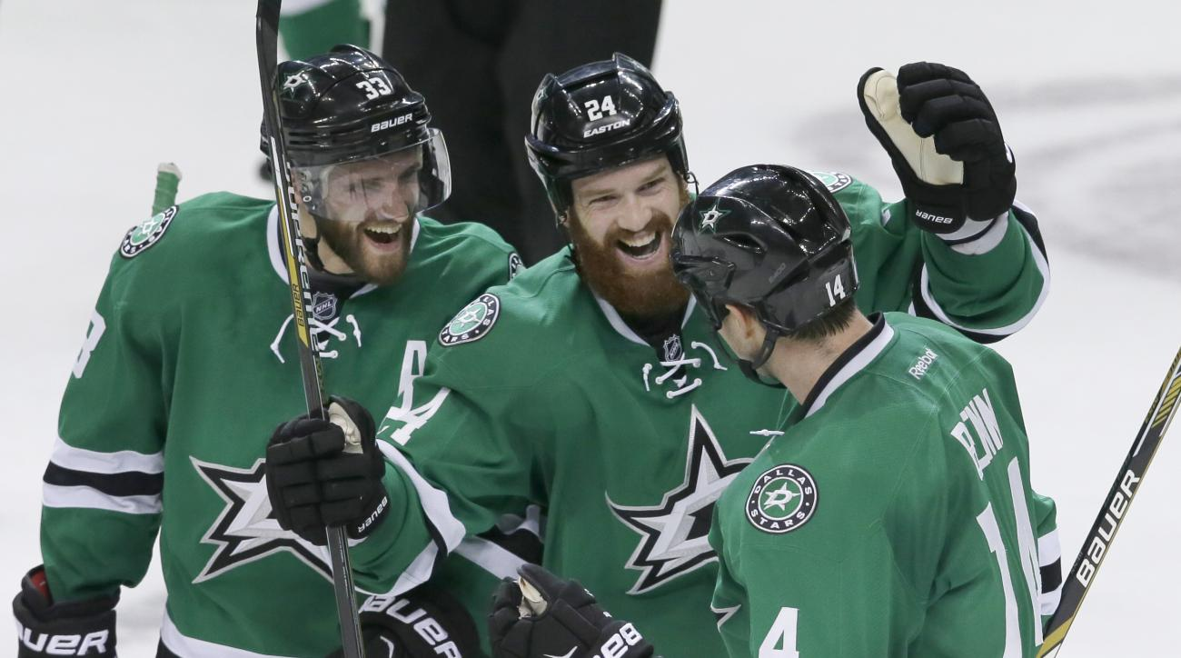 Dallas Stars left wing Jamie Benn (14) celebrates his goal with teammates Alex Goligoski and Jordie Benn (24) during overtime play of an NHL hockey game, against the Vancouver Canucks Thursday, Oct. 29, 2015, in Dallas. The Stars won 4-3.(AP Photo/LM Oter