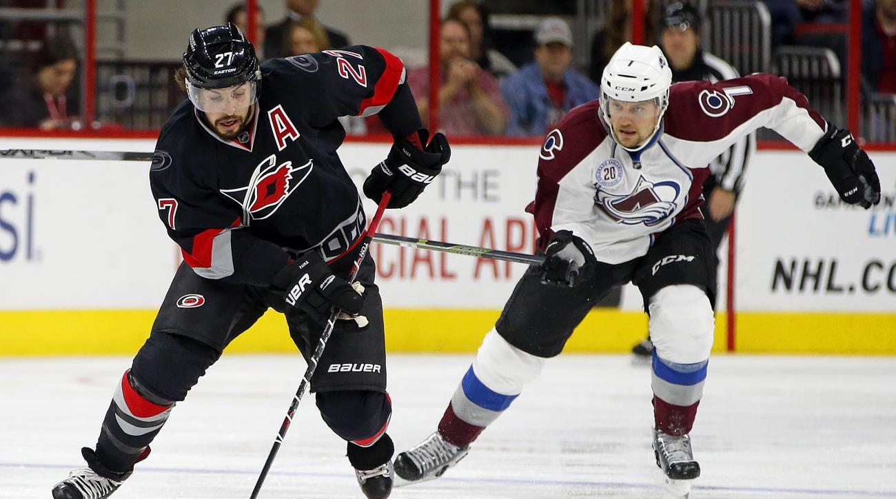 Carolina Hurricanes' Justin Faulk, left, moves the puck with Colorado Avalanche's John Mitchell, right,  closing in during the second period of an NHL hockey game, Friday, Oct. 30, 2015, in Raleigh, N.C. (AP Photo/Karl B DeBlaker)