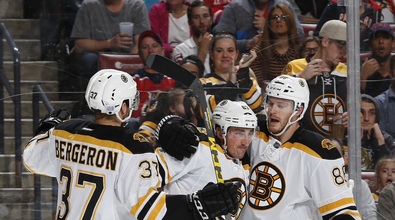 Boston Bruins forward Brad Marchand (63) is congratulated by Kevan Miller (86) and center Patrice Bergeron (37) after he scored his second goal against the Florida Panthers during the second period of an NHL hockey game, Friday, Oct. 30, 2015, in Sunrise,