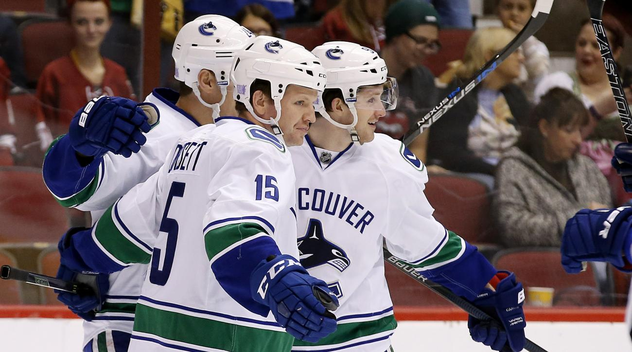 Vancouver Canucks' Jared McCann, right, celebrates his goal against the Arizona Coyotes with Derek Dorsett (15) and Adam Cracknell, left, during the first period of an NHL hockey game Friday, Oct. 30, 2015, in Glendale, Ariz. (AP Photo/Ross D. Franklin)