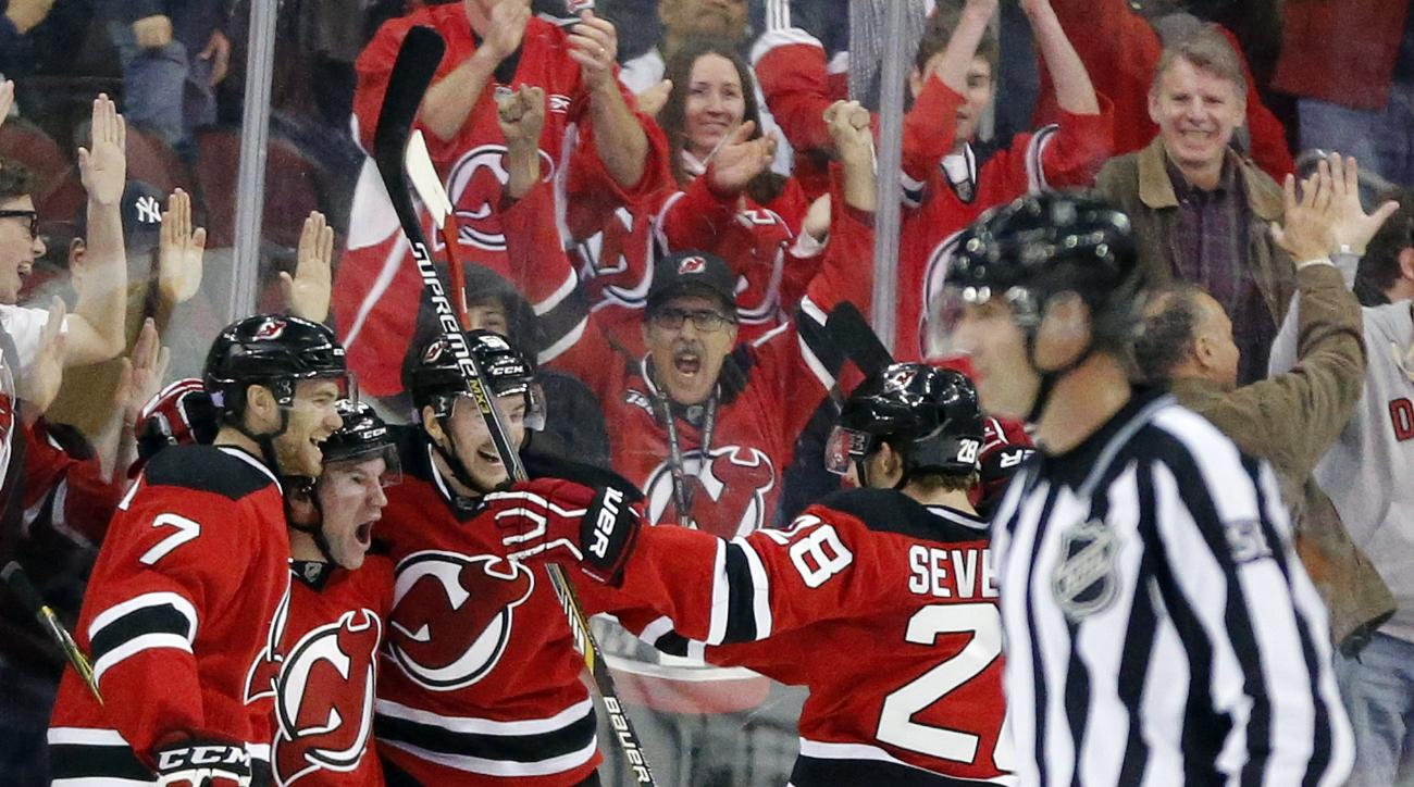 New Jersey Devils, from left, Jon Merrill Bobby Farnham, Sergey Kalinin, of Russia, and Damon Severson celebrate Franham's goal against the New York Islanders during the first period of an NHL hockey game, Saturday, Oct. 31, 2015, in Newark, N.J. (AP Phot