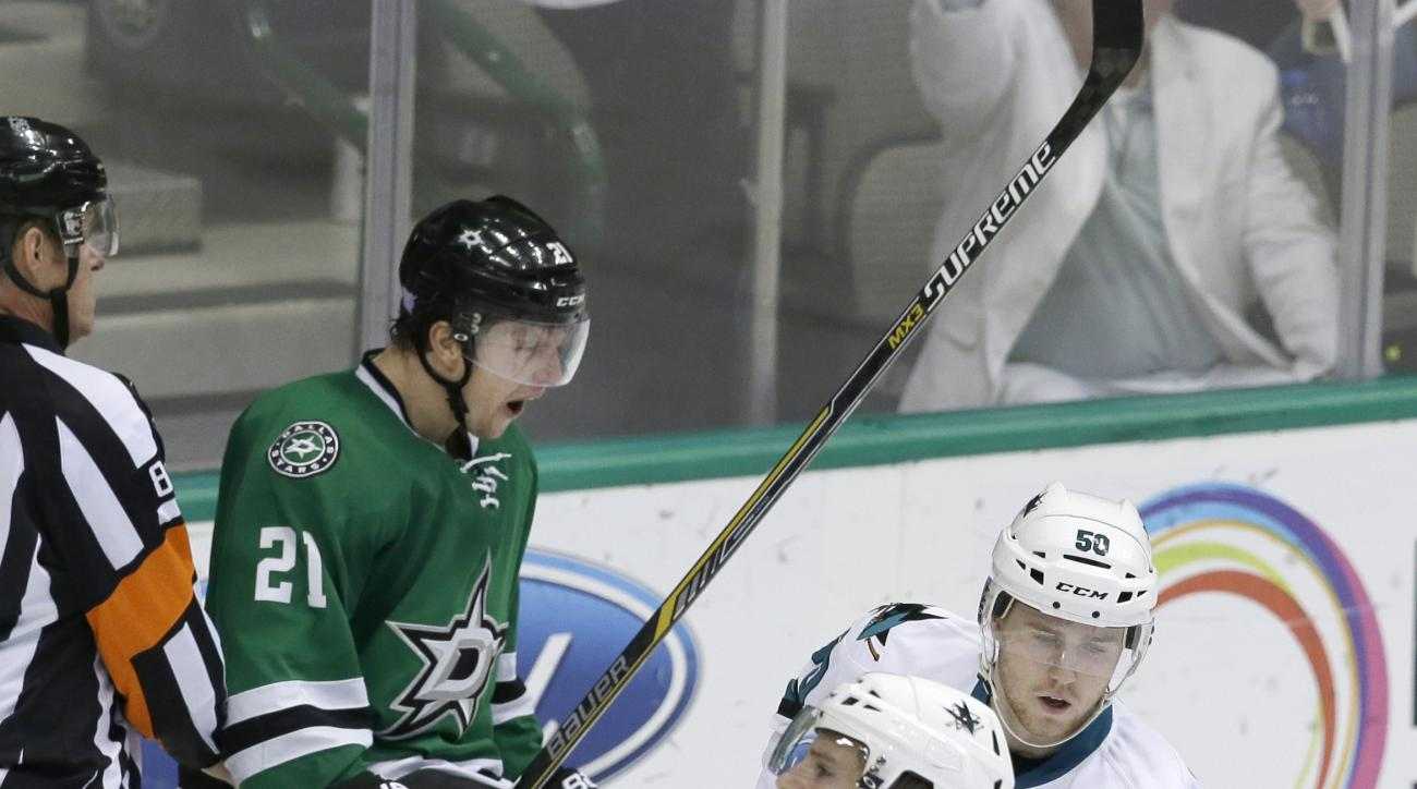 Dallas Stars left wing Antoine Roussel (21) celebrates after scoring a goal in front of San Jose Sharks Tommy Wingels (57) and Chris Tierney (50) during the third period of an NHL hockey game Saturday, Oct. 31, 2015, in Dallas. (AP Photo/LM Otero)