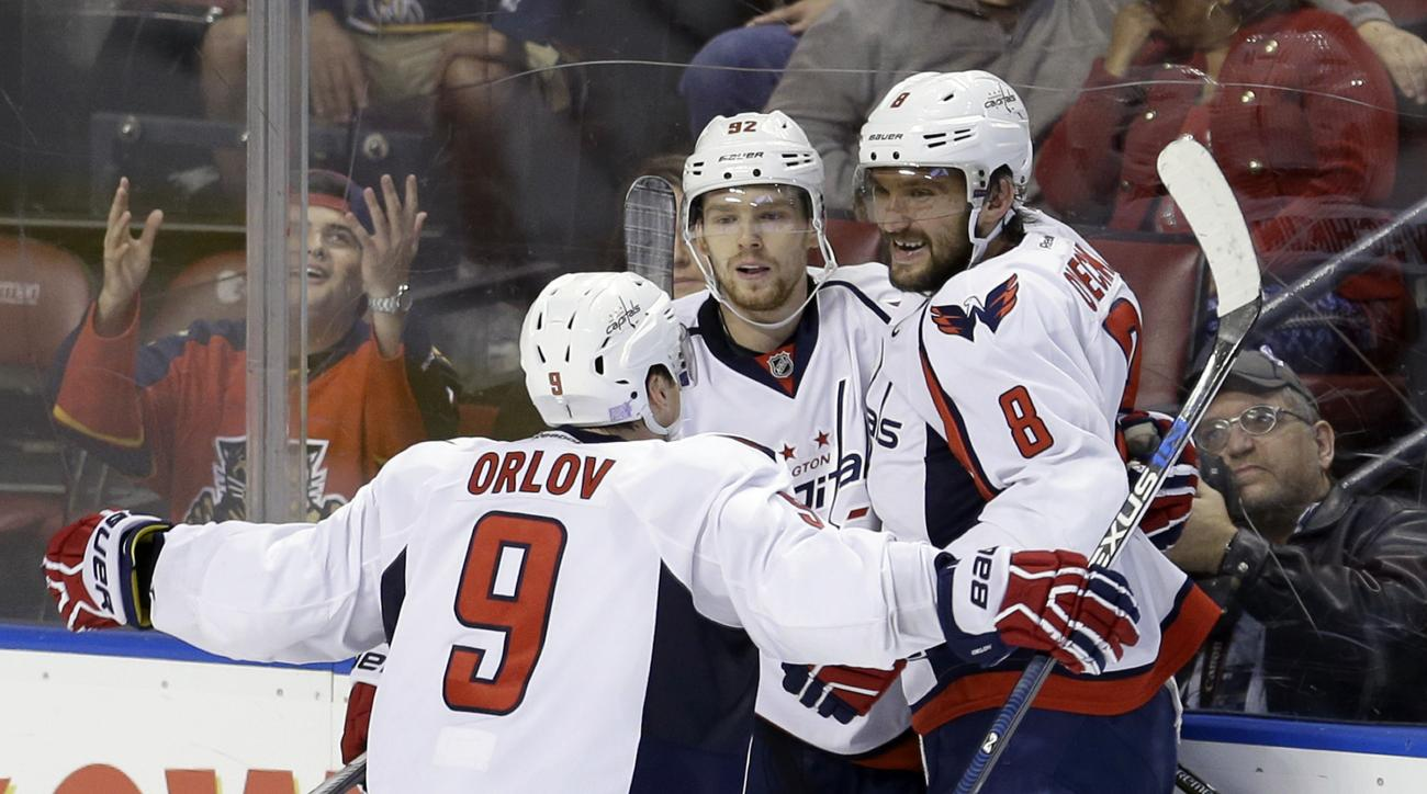 Washington Capitals defenseman Dmitry Orlov (9) and Alex Ovechkin (8) congratulate Evgeny Kuznetsov (92) after Kuznetsov scored the game-winning, 2-1, goal against the Florida Panthers in overtime of an NHL hockey  game, Saturday, Oct. 31, 2015, in Sunris
