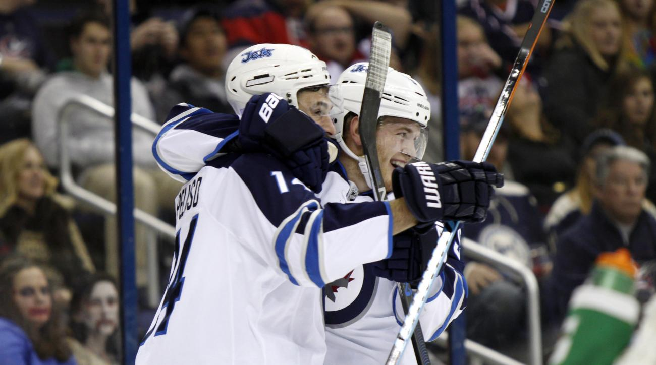 Winnipeg Jets' Andrew Copp, right, celebrates with teammate Anthony Peluso after scoring a goal against the Columbus Blue Jackets during the first period of an NHL hockey game in Columbus, Ohio, Saturday, Oct. 31, 2015. Winnipeg won 3-2.  (AP Photo/Paul V