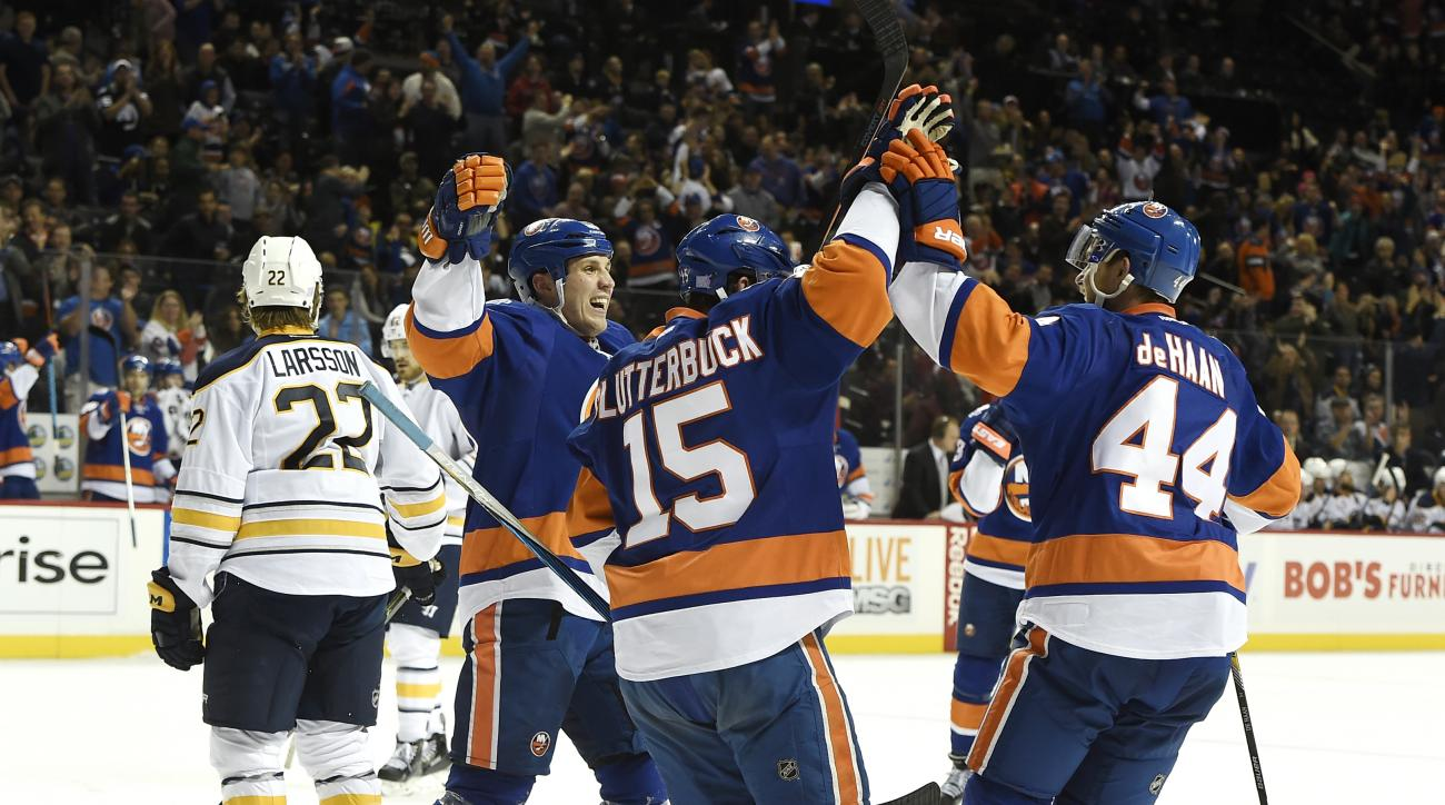 New York Islanders center Casey Cizikas (53), right wing Cal Clutterbuck (15) and  defenseman Calvin de Haan (44) celebrate  de Haan's goal as Buffalo Sabres left wing Johan Larsson (22) skates away during the second period of an NHL hockey game on Sunday