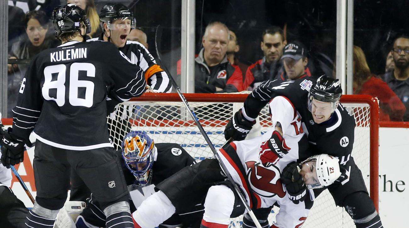 New York Islanders defenseman Calvin de Haan (44) restrains New Jersey Devils right wing Kyle Palmieri (21), bringing him to the ice during the second period of an NHL hockey game in New York, Tuesday, Nov. 3, 2015. (AP Photo/Kathy Willens)
