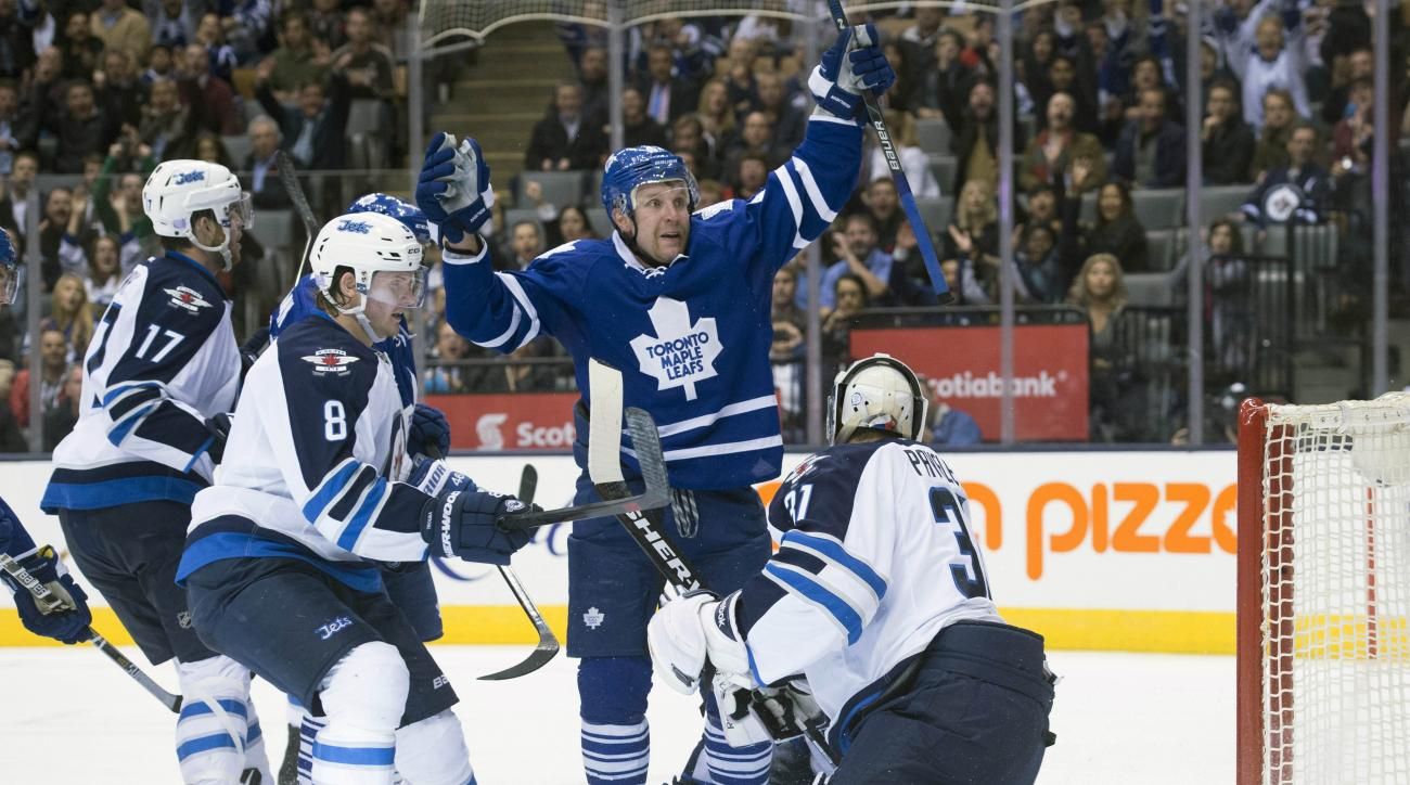 Toronto Maple Leafs' Leo Komarov, second from right, celebrates a goal in front of Winnipeg Jets' Adam Lowry, left to right, Jacob Trouba and goaltender Ondrej Pavelec during the second period of an NHL hockey game in Toronto, Wednesday, Nov. 4, 2015. (Da