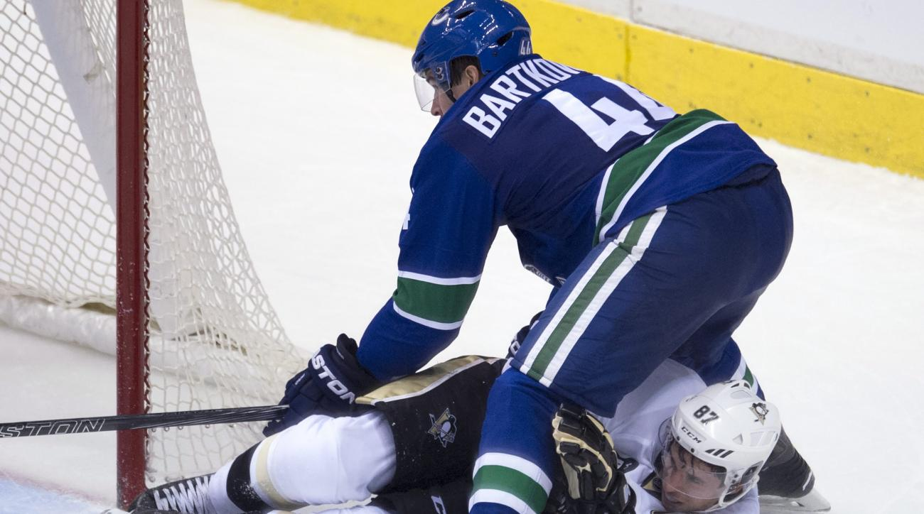 Pittsburgh Penguins center Sidney Crosby (87) vies for control of the puck with Vancouver Canucks defenseman Matt Bartkowski (44) during the third period of an NHL hockey game Wednesday, Nov. 4, 2015, in Vancouver, British Columbia. (Jonathan Hayward/The