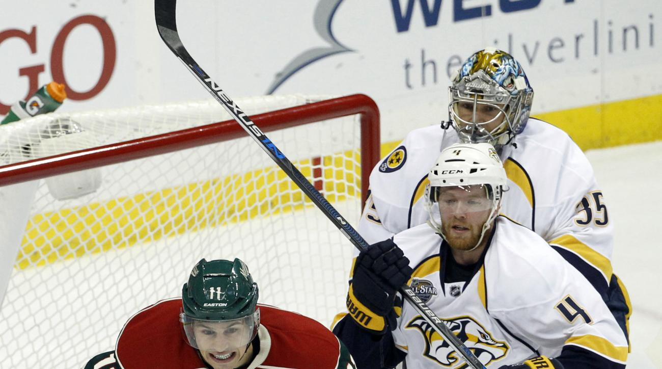 Minnesota Wild left wing Zach Parise, left, chases the puck in front of Nashville Predators defenseman Ryan Ellis, center, as Predators goalie Pekka Rinne, right, of Finland, tries to get back in the net during the first period of an NHL hockey game in St