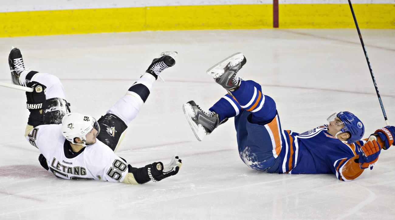 Pittsburgh Penguins' Kris Letang (58) and Edmonton Oilers' Taylor Hall (4) fall after colliding during the second period of an NHL hockey game Friday, Nov. 6, 2015, in Edmonton, Alberta. (Jason Franson/The Canadian Press via AP)