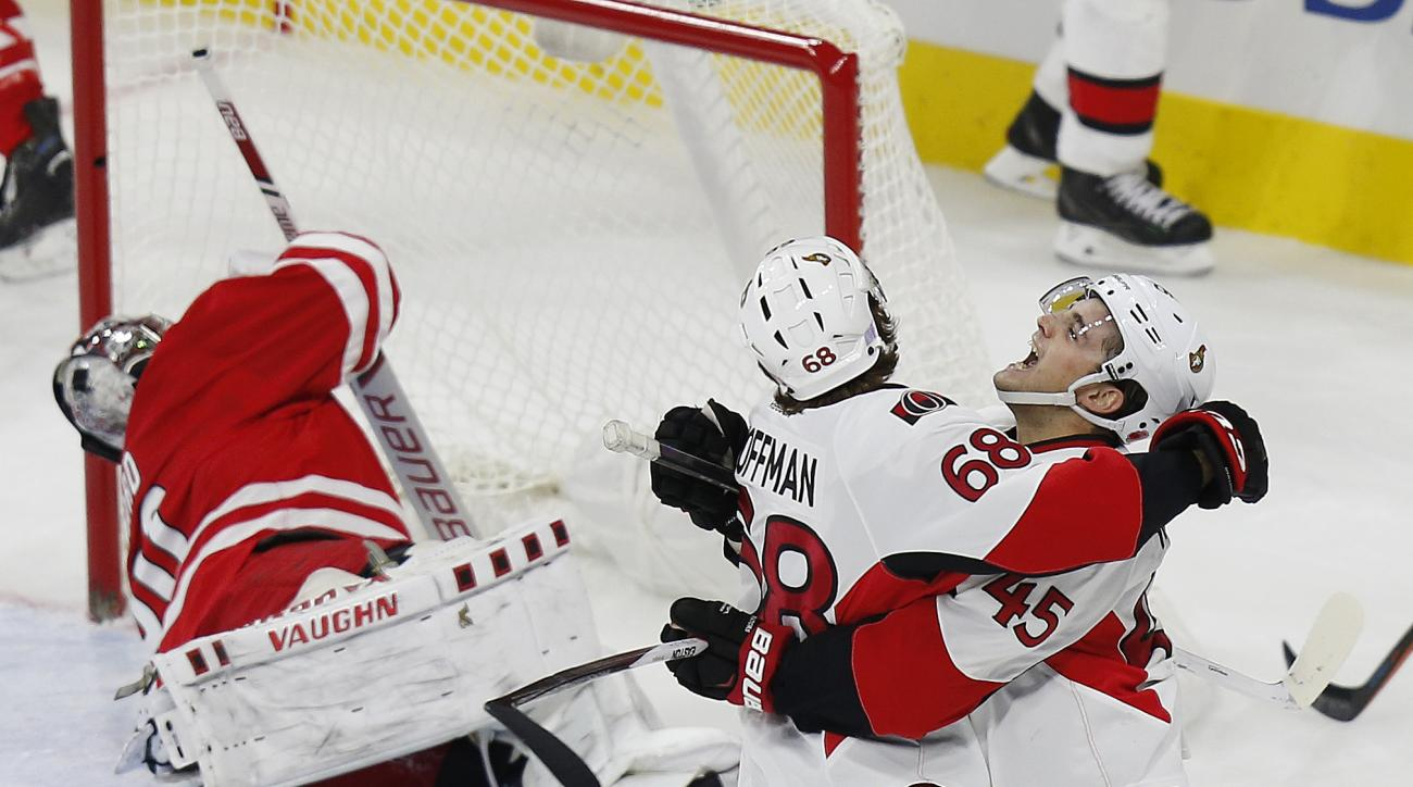 Ottawa Senators' Chris Wideman (45) celebrates with teammate Mike Hoffman (68) after scoring a second-period goal against Carolina Hurricanes goaltender Cam Ward, left, during an NHL hockey game in Raleigh, N.C., Saturday, Nov. 7, 2015. (AP Photo/Ellen Oz