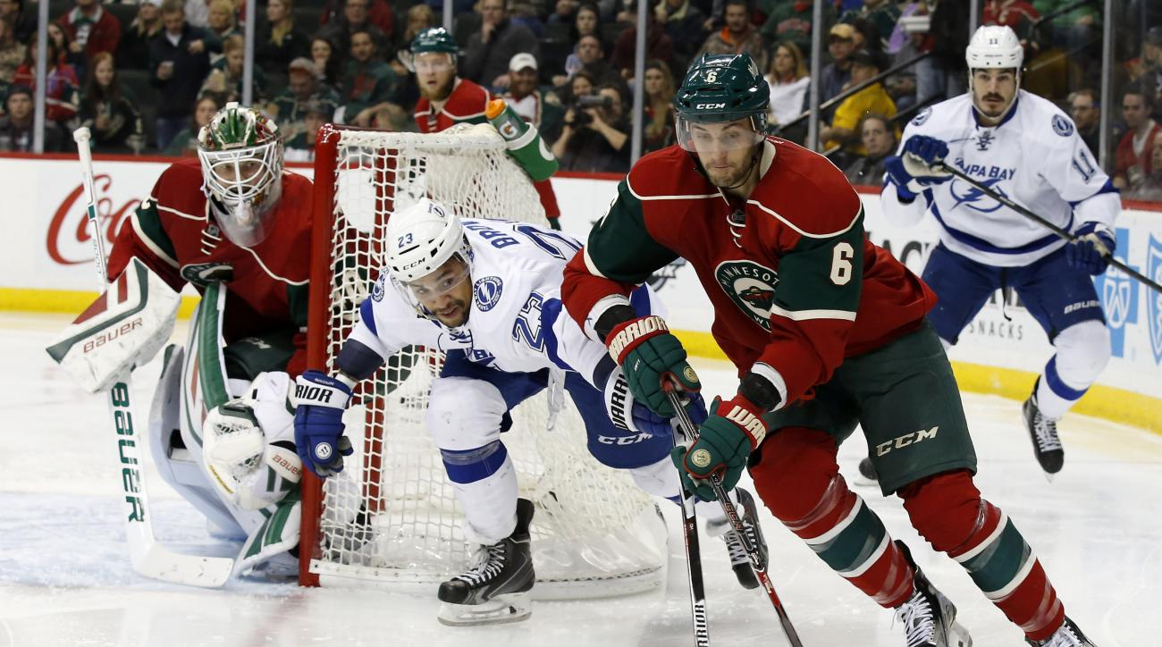Minnesota Wild defenseman Marco Scandella (6) controls the puck in front of Tampa Bay Lightning right wing J.T. Brown (23) as  Wild goalie Devan Dubnyk, left, covers the net during the second period of an NHL hockey game in St. Paul, Minn., Saturday, Nov.