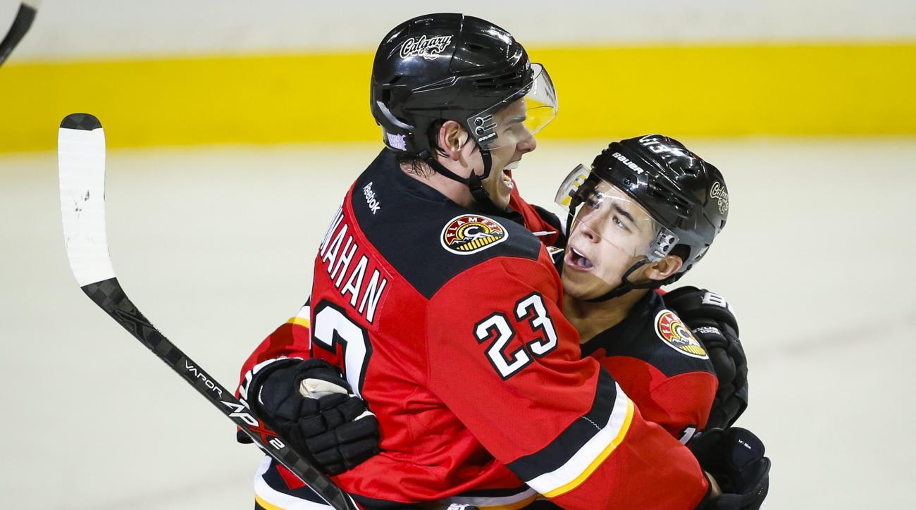 Calgary Flames' Johnny Gaudreau, right, celebrates his goal against the Pittsburgh Penguins with teammate Sean Monahan during first period NHL hockey action, in Calgary, on Saturday, Nov. 7, 2015. (Jeff McIntosh/The Canadian Press via AP)