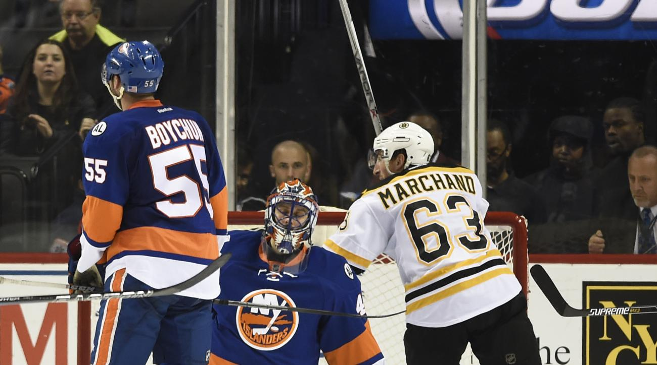Boston Bruins' Brad Marchand (63) celebrates his goal as New York Islanders goalie Jaroslav Halak (41) and Johnny Boychuk (55) react during the second period of an NHL hockey game on Sunday, Nov. 8, 2015, in New York. (AP Photo/Kathy Kmonicek)