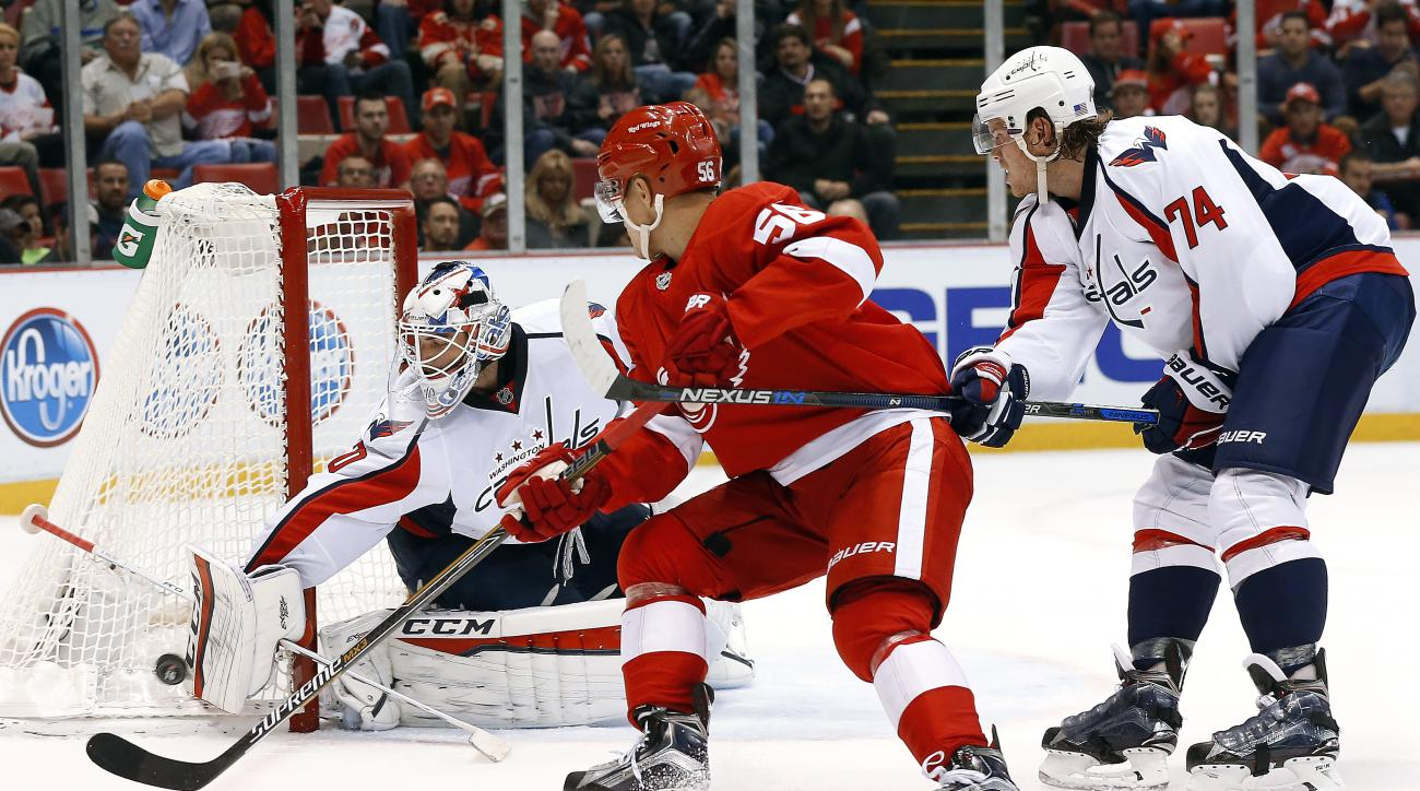 Washington Capitals goalie Braden Holtby (70) stops a Detroit Red Wings left wing Teemu Pulkkinen (56) shot as John Carlson (74) defends in the second period of an NHL hockey game Tuesday, Nov. 10, 2015, in Detroit. (AP Photo/Paul Sancya)