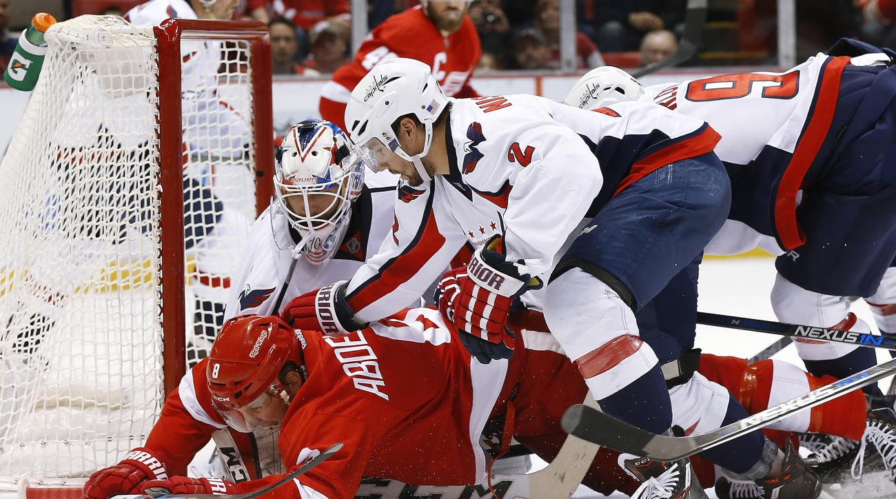 Detroit Red Wings left wing Justin Abdelkader (8) is checked to the ice by defenseman Matt Niskanen (2) after Washington Capitals goalie Braden Holtby stopped his shot in the second period of an NHL hockey game Tuesday, Nov. 10, 2015, in Detroit. (AP Phot