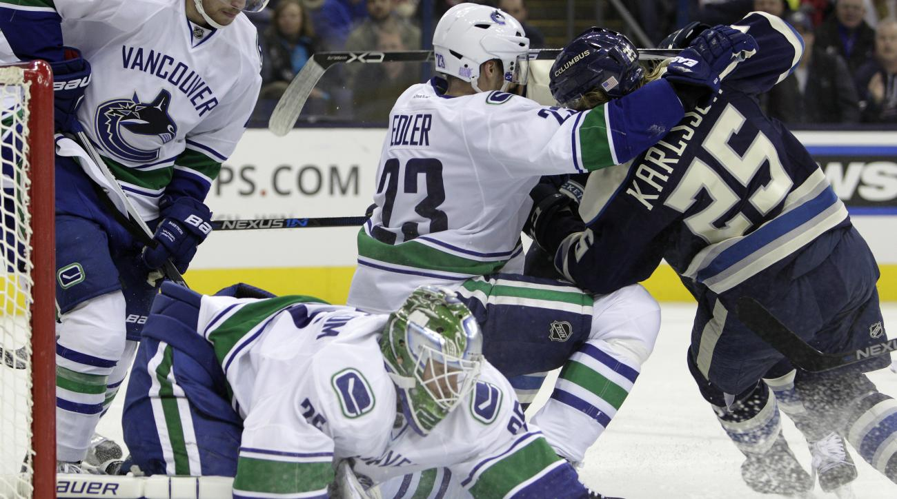 Vancouver Canucks' Jacob Markstrom, front, of Sweden, covers the puck as teammate Alexander Edler, center, and Columbus Blue Jackets' William Karlsson, of Sweden, vie for position during the second period of an NHL hockey game Tuesday, Nov. 10, 2015, in C