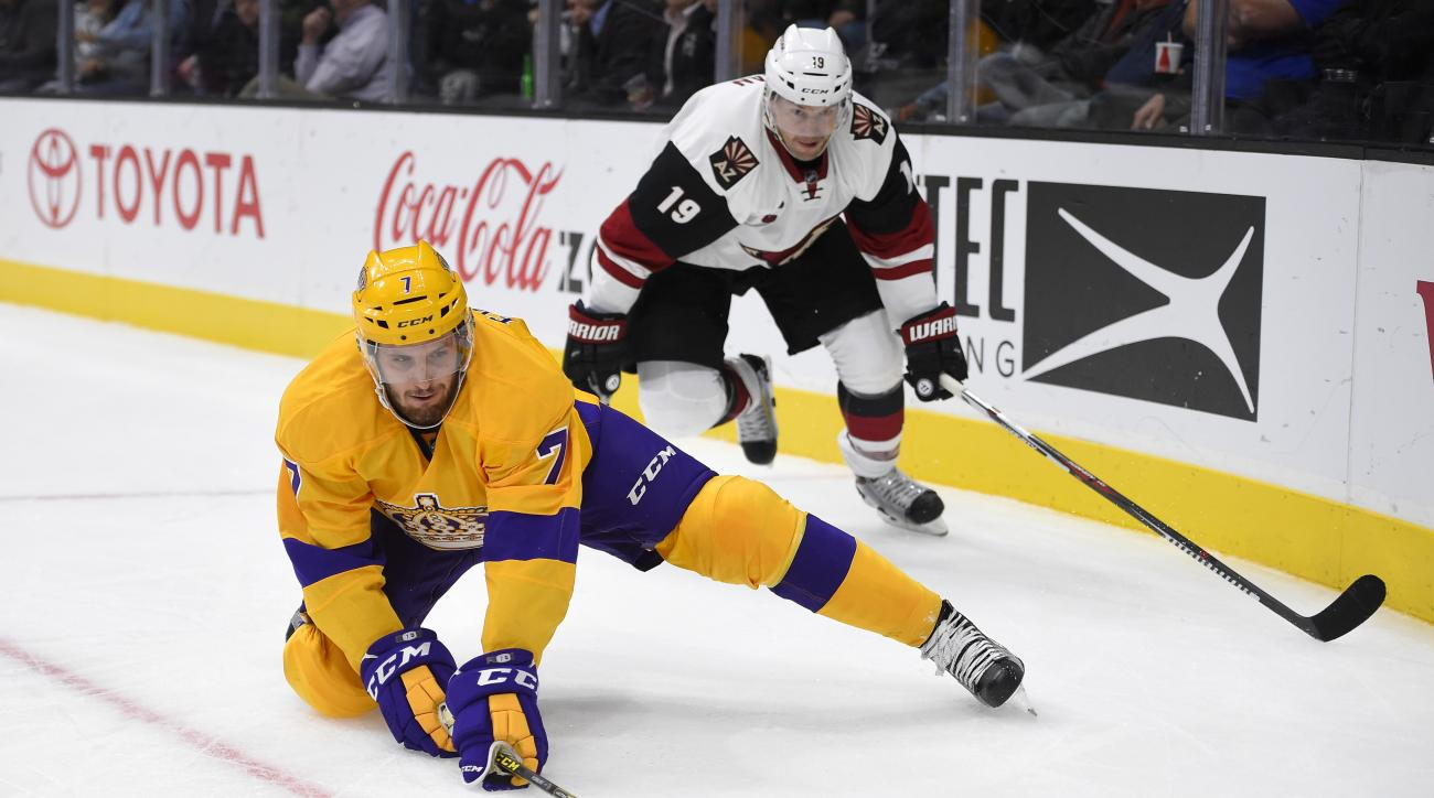 Los Angeles Kings defenseman Derek Forbort, left, passes the puck from his knees under pressure from Arizona Coyotes right wing Shane Doan during the third period of an NHL hockey game, Tuesday, Nov. 10, 2015, in Los Angeles. The Coyotes won 3-2. (AP Phot