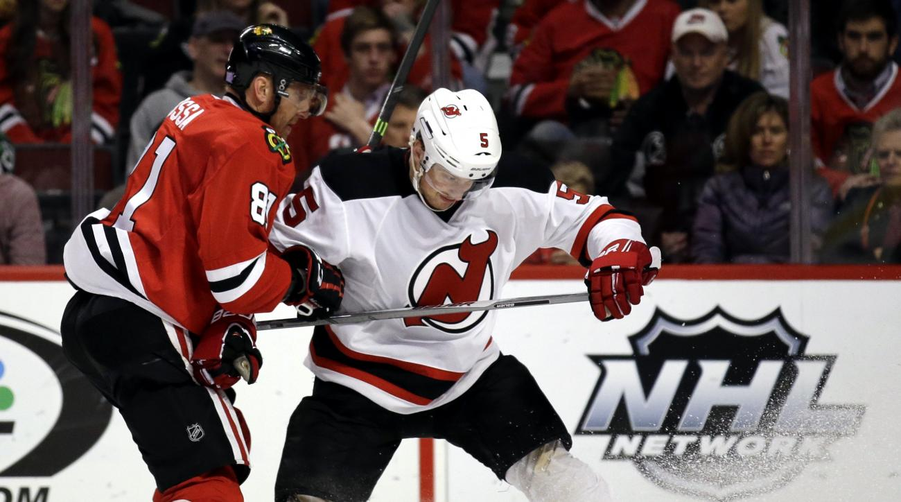 New Jersey Devils defenseman Adam Larsson, right, and Chicago Blackhawks right wing Marian Hossa vie for the puck during the second period of an NHL hockey game Thursday, Nov. 12, 2015, in Chicago. (AP Photo/Nam Y. Huh)