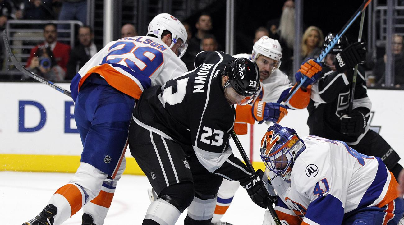 New York Islanders goalie Jaroslav Halak (41), of Slovakia, stops a shot as Los Angeles Kings right wing Dustin Brown (23) looks for a rebound next to Islanders center Brock Nelson (29) during the second period of an NHL hockey game in Los Angeles, Thursd