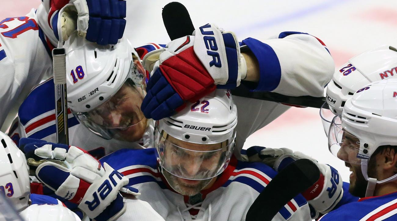 New York Rangers' Dan Boyle, center, celebrates his shoot-out goal with teammates during overtime NHL hockey action against the Ottawa Senators, in Ottawa, on Saturday, Nov. 14, 2015. The Rangers beat the Senators 2-1. (Fred Chartrand/The Canadian Press v