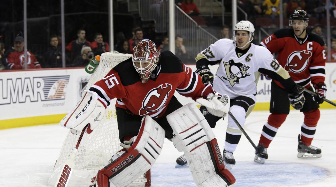 New Jersey Devils goalie Cory Schneider (35) turns away the puck in front of Pittsburgh Penguins center Sidney Crosby (87) during the first period of an NHL hockey game Saturday, Nov. 14, 2015, in Newark, N.J. (AP Photo/Adam Hunger)