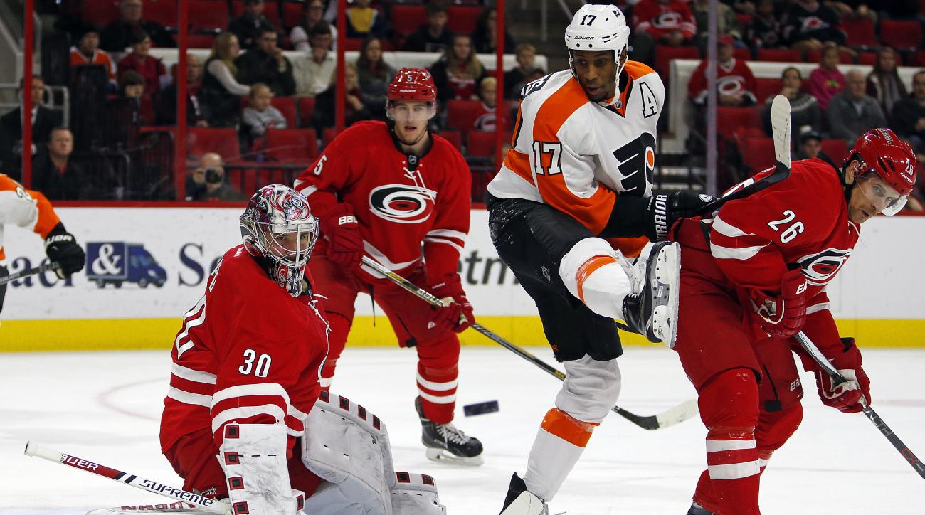 Carolina Hurricanes goalie Cam Ward (30) clears the puck as teammate John-Michael Liles (26) battles Philadelphia Flyers' Wayne Simmonds (17) during the second period of an NHL hockey game, Saturday, Nov. 14, 2015, in Raleigh, N.C. (AP Photo/Karl B DeBlak