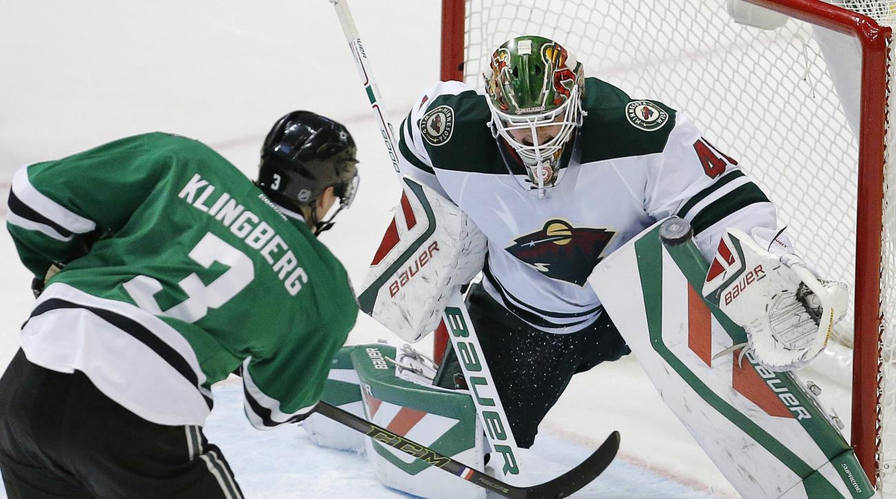 Dallas Stars defenseman John Klingberg (3) shoots the puck past Minnesota Wild goalie Devan Dubnyk (40) to score the game-winning goal in overtime during an NHL hockey game, Saturday, Nov. 14, 2015, in Dallas. Dallas won 3-2. (AP Photo/Brandon Wade)