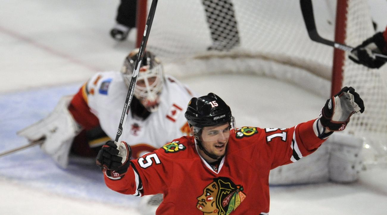 Chicago Blackhawks' Artem Anisimov (15), of Russia, celebrates after teammate Patrick Kane scored a goal during the second period of an NHL hockey game against the Calgary Flames, Sunday, Nov. 15, 2015, in Chicago. (AP Photo/Paul Beaty)