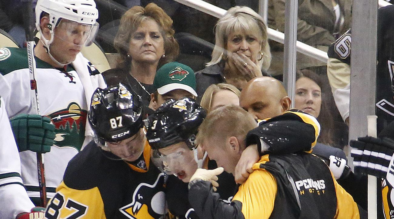 Pittsburgh Penguins' Olli Maatta, center, is helped off the ice by a team trainer, right, and Sidney Crosby (87) after being injured during the second period of an NHL hockey game against the Minnesota Wild in Pittsburgh Tuesday, Nov. 17, 2015. Maatta was