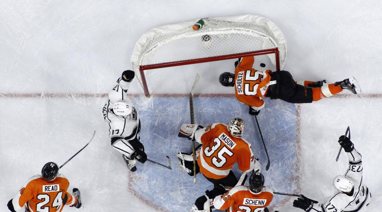 Los Angeles Kings' Milan Lucic (17) and Tyler Toffoli (73) celebrate after Lucic's goal against Philadelphia Flyers' Steve Mason (35) as Luke Schenn (22), Nick Schultz (55), and Matt Read (24) defend during the third period of an NHL hockey game, Tuesday,