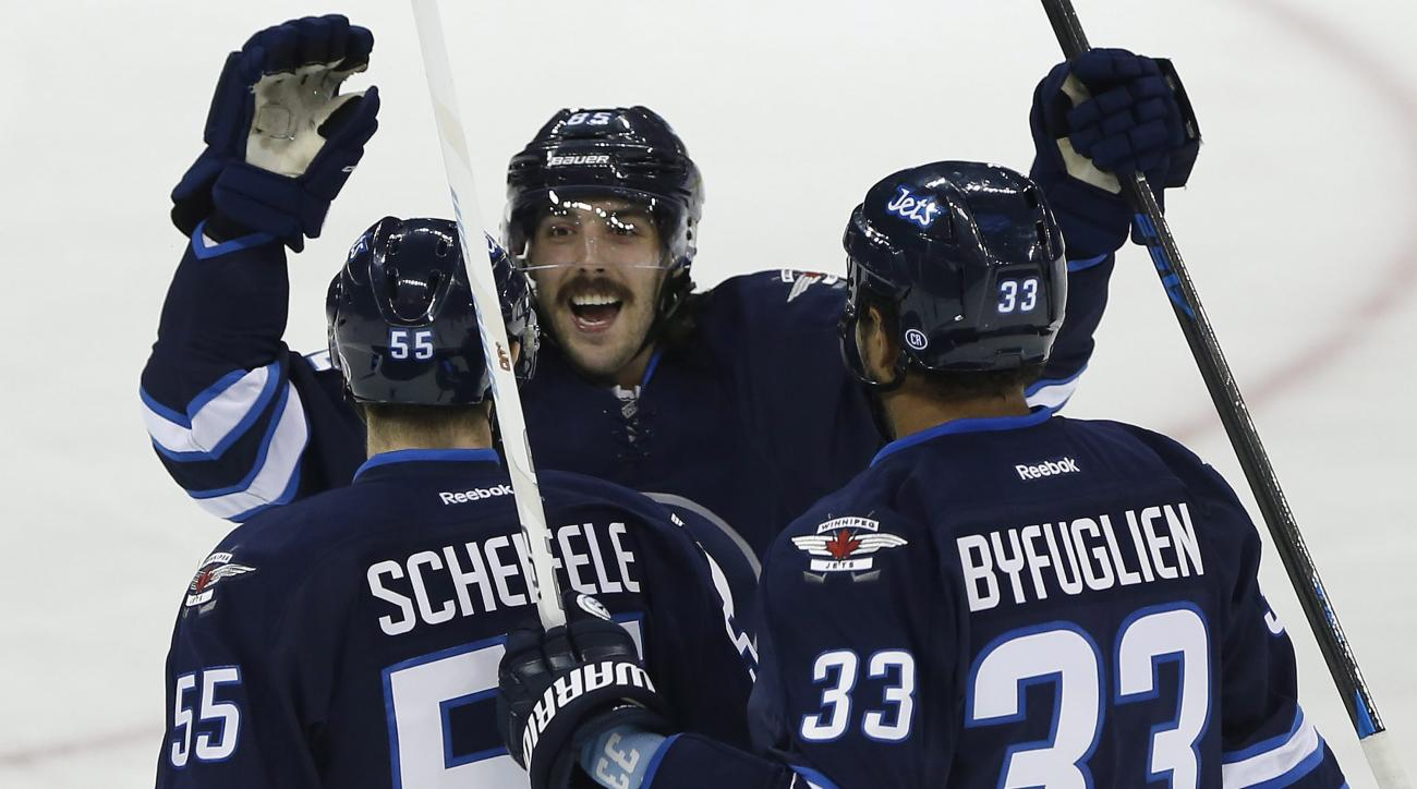 Winnipeg Jets' Mark Scheifele (55), Mathieu Perreault (85) and Dustin Byfuglien (33) celebrate Scheifele's goal against the Vancouver Canucks during the first period of an NHL hockey game in Winnipeg, Manitoba, Wednesday, Nov. 18, 2015. (John Woods/The Ca
