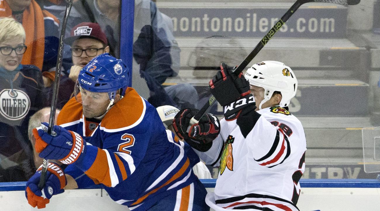 Chicago Blackhawks' Ryan Garbutt (28) checks Edmonton Oilers' Andrej Sekera (2) during second period NHL action in Edmonton, Alberta, on Wednesday, Nov. 18, 2015. (Jason Franson/The Canadian Press via AP)
