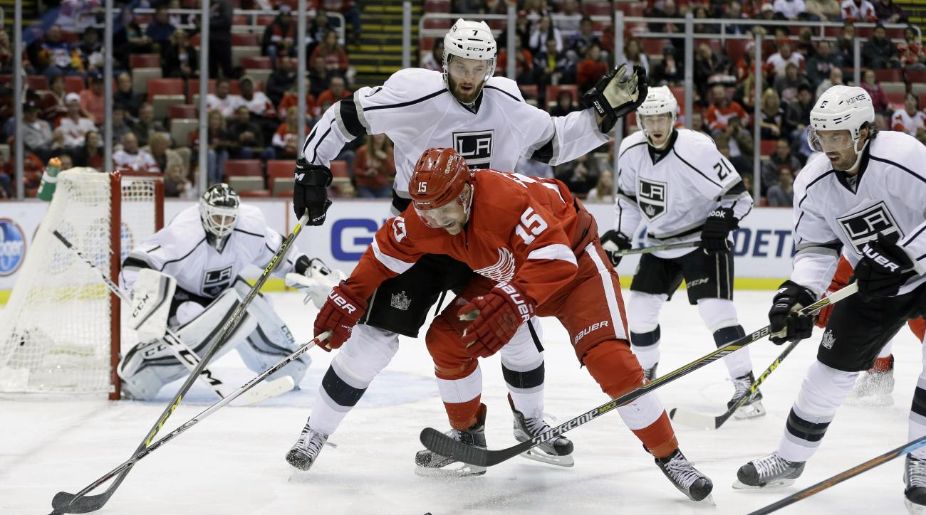 Detroit Red Wings center Riley Sheahan (15) fights for the puck with Los Angeles Kings defensemen Derek Forbort (7) and Jamie McBain (5) during the second period of an NHL hockey game, Friday, Nov. 20, 2015, in Detroit. (AP Photo/Carlos Osorio)