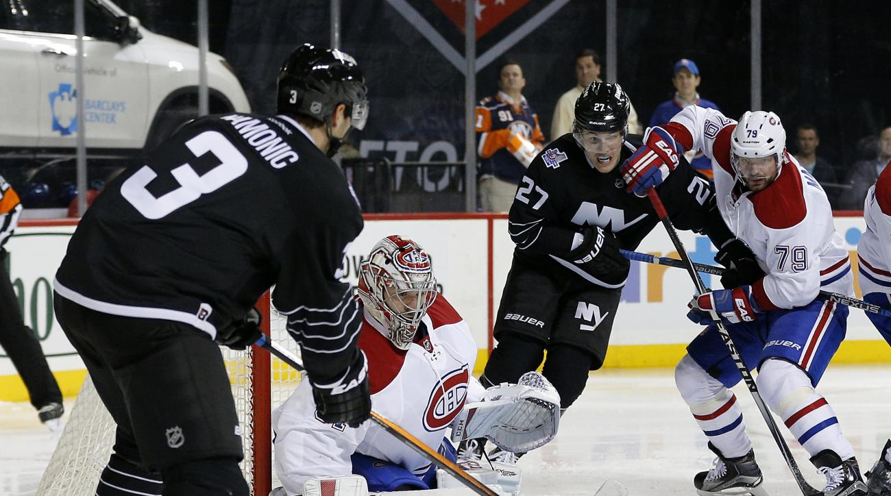 Montreal Canadiens goalie Carey Price (31) stops a shot by New York Islanders defenseman Travis Hamonic (3) as Canadiens defenseman Andrei Markov (79) tries to keep Islanders center Anders Lee (27) away from the crease during the second period of an NHL h