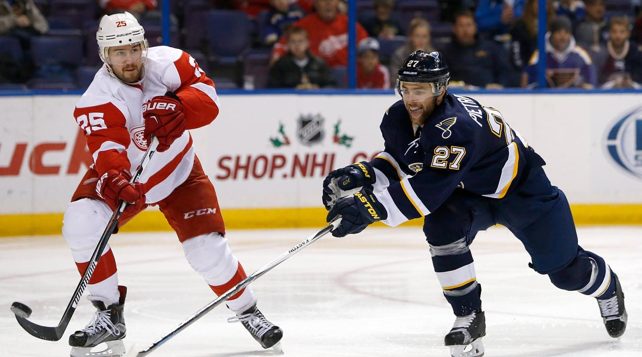 Detroit Red Wings' Mike Green, left, lifts the puck past St. Louis Blues' Alex Pietrangelo during the second period of an NHL hockey game Saturday, Nov. 21, 2015, in St. Louis. (AP Photo/Scott Kane)