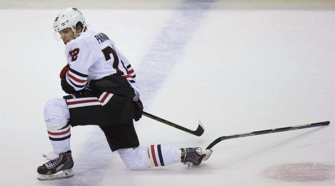 Chicago Blackhawks' Artemi Panarin, of Russia, gets the stick of Vancouver Canucks' Chris Higgins caught in his skate during the second period of an NHL hockey game Saturday, Nov. 21, 2015, in Vancouver, British Columbia. (Darryl Dyck/The Canadian Press v