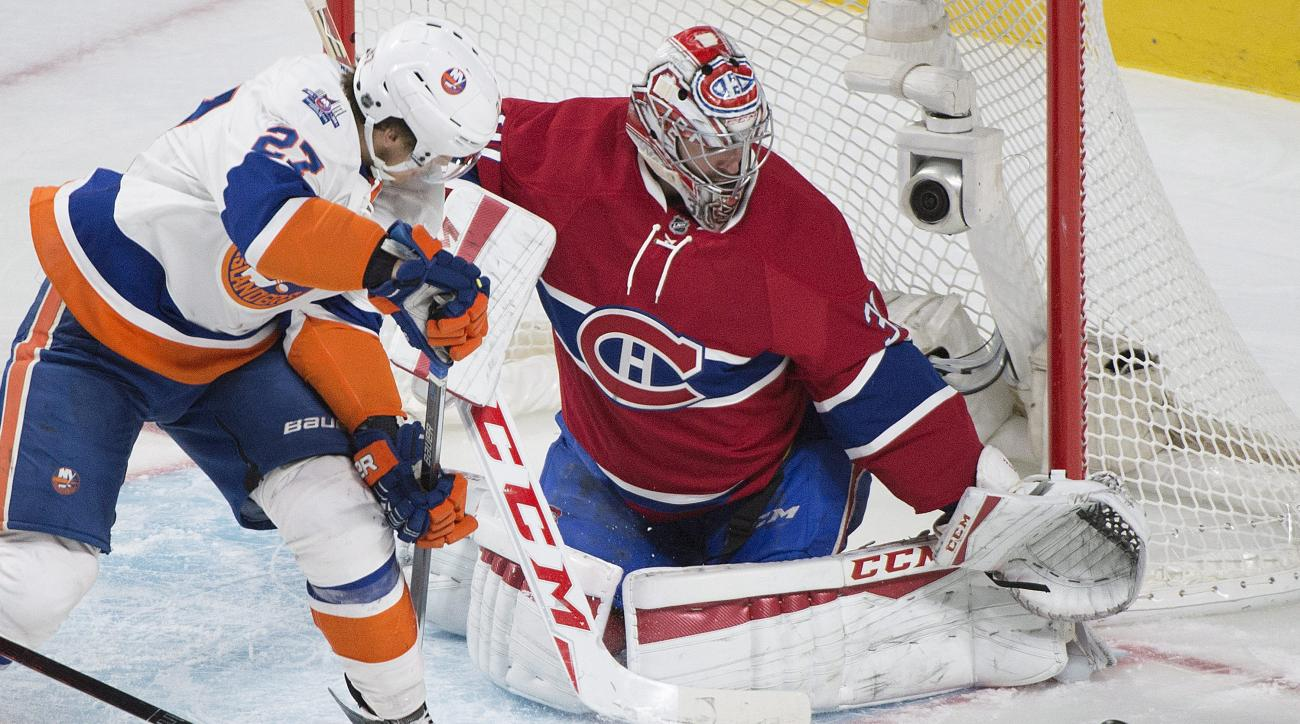 Montreal Canadiens goaltender Carey Price makes a save against New York Islanders' Anders Lee during the third period of an NHL hockey game in Montreal on Sunday, Nov. 22, 2015. (Graham Hughes/The Canadian Press via AP)